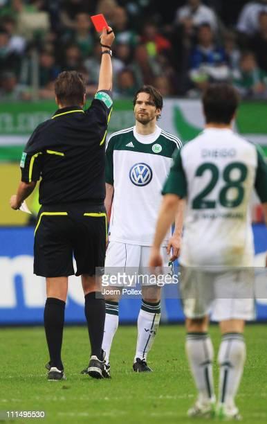 Arne Friedrich of Wolfsburg gets the red card from referee Thorsten Kinhoefer during the Bundesliga match between VfL Wolfsburg and Eintracht...