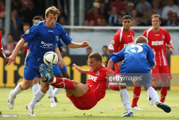 Arne Janssen and Artur Zimmermann of Emden and Lukas Podolski of Koeln compete for the ball during the DFB Cup first round match between BSV Kickers...