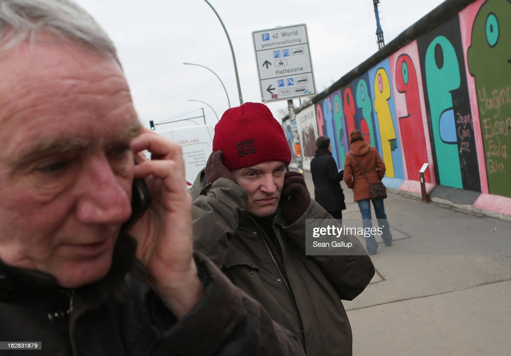 Arno Paulus (L), a local real estate development opponent, and Thierry Noir, the artist who painted the murals visible behind, make phone calls while standing next to the East Side Gallery, which is the longest still-standing portion of the former Berlin Wall, close to where a new hotel is scheduled to be built on February 28, 2013 in Berlin, Germany. According to media reports the developer in charge of the project plans to remove an approximately 25-meter long piece of the Wall and transfer it elsewhere in order to allow access to the construction site. Critics, including East Side Gallery mural artists and Spree River embankment development opponents, decry the move, citing the East Side Gallery's status as a protected landmark and a majortourist attraction.