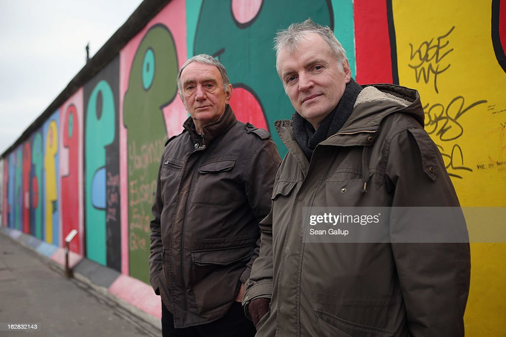 Arno Paulus (L), a local real estate development opponent, and Thierry Noir, the artist who painted the murals visible behind, pose next to the East Side Gallery, which is the longest still-standing portion of the former Berlin Wall, close to where a new hotel is scheduled to be built on February 28, 2013 in Berlin, Germany. According to media reports the developer in charge of the project plans to remove an approximately 25-meter long piece of the Wall and transfer it elsewhere in order to allow access to the construction site. Critics, including East Side Gallery mural artists and Spree River embankment development opponents, decry the move, citing the East Side Gallery's status as a protected landmark and a majortourist attraction.