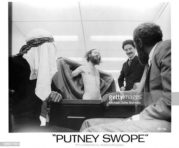 Arnold Johnson watching a flasher in a scene from the film 'Putney Swope' 1969