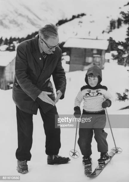 Arnold Lunn President of the Kandahar Ski Racing Club giving 4 year old Teddie Tulloch a lesson at the Palace Hotel in Murren where the club has its...