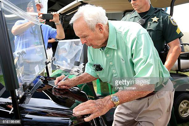 Arnold Palmer autographs a golf cart during the first round of the Arnold Palmer Invitational Presented by MasterCard at Bay Hill Club and Lodge on...