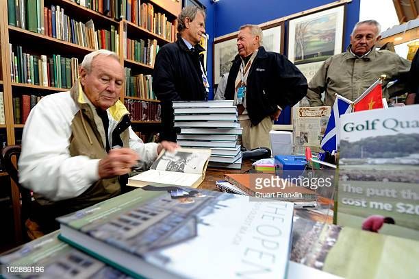 Arnold Palmer autographs books for fans at the merchandise pavilion during practice for the 139th Open Championship on the Old Course St Andrews on...