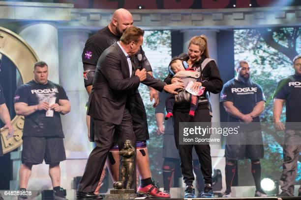 Arnold Schwarzenegger examines the infant son of Brian Shaw who is held by Shaw's wife after Shaw won the 2017 Arnold Strongman Classic as part of...