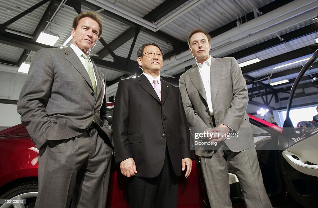 Arnold Schwarzenegger, governor of California, left, Akio Toyoda, president of Toyota Motor Corp., center, and, Elon Musk, chairman and chief executive officer of Tesla Motors Inc., pose in front of a Tesla Motors Inc.' s Model S electric car at Tesla Motors Inc.'s headquarters in Palo Alto, California, U.S., on Thursday, May 20, 2010. Toyota Motor Corp. will acquire a $50 million stake in California electric-car maker Tesla Motors Inc. as automakers compete to introduce less-polluting vehicles in the U.S. Photographer: Tony Avelar/Bloomberg via Getty Images