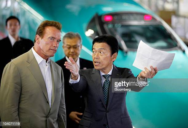 Arnold Schwarzenegger governor of California left listens to Masaki Ogata vice president of East Japan Railway Co during an inspection of Japan's...