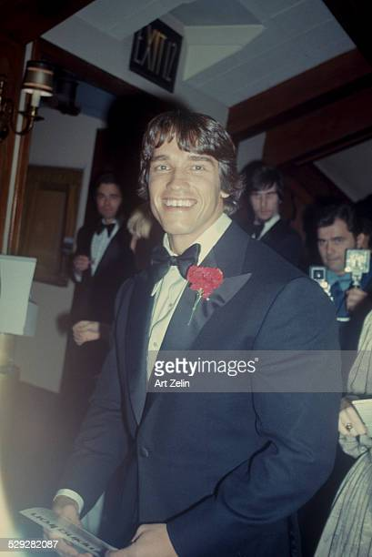 Arnold Schwarzenegger in a tux with a red carnation circa 1970 New York