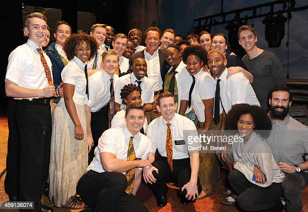 Arnold Schwarzenegger poses with cast members backstage at the West End production of 'The Book Of Mormon' at The Prince of Wales Theatre on November...