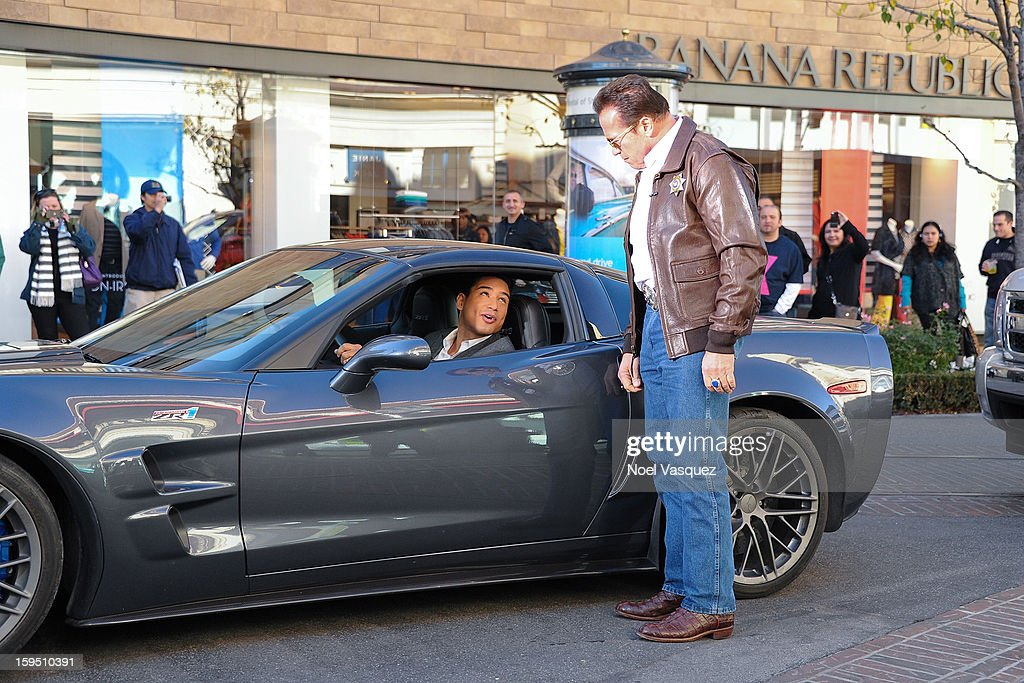 Arnold Schwarzenegger (R) pulls over Mario Lopez at Extra at The Grove on January 14, 2013 in Los Angeles, California.