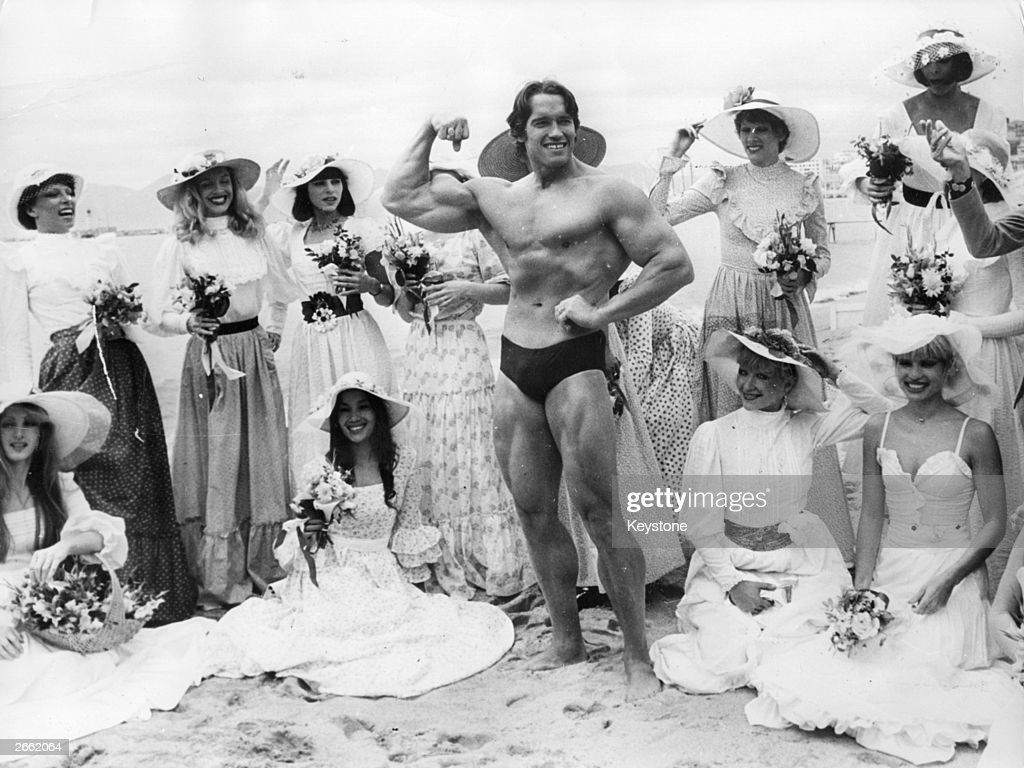 <a gi-track='captionPersonalityLinkClicked' href=/galleries/search?phrase=Arnold+Schwarzenegger&family=editorial&specificpeople=156406 ng-click='$event.stopPropagation()'>Arnold Schwarzenegger</a>, the film actor who first became famous as Mr Universe for his magnificent physique, on Cannes beach during the Film Festival with the girls from the Folies Bergere.