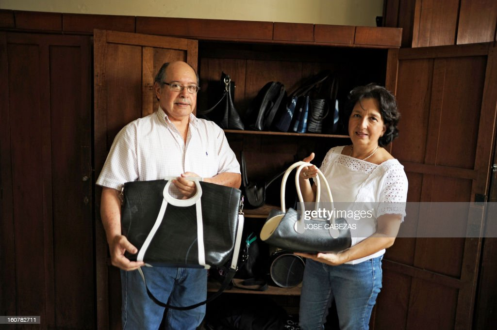 Arnoldo Ruffatti (L) and Maria de Los Angeles Ruffatti (R), owners of Uca Ruffatti Manufacturas, pose for a pictures with their products made out of car and truck inner tubes at their factory in Santa Ana, 60 km west from San Salvador, El Salvador, on February 5, 2013. Uca Ruffatti Manufacturas have been making handbags and accesories for over 20 years. Their handbags made out of discarded inner tubes are being exported to Europe and the US. AFP PHOTO/ Jose CABEZAS