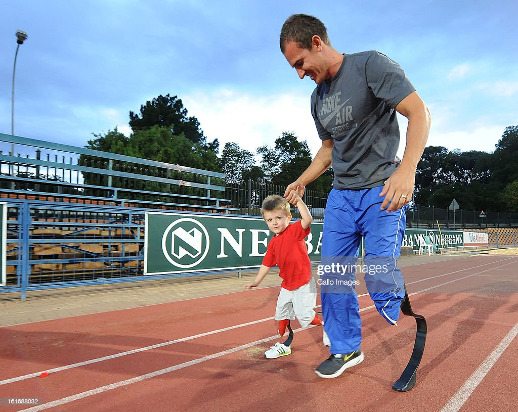 Arnu Fourie walks with double amputee William le Roux, 3, during day 4 of The Nedbank National Championships for the Physically Disabled (Athletics) at LC de Villiers Stadium on March 26, 2013 in Pretoria, South Africa.