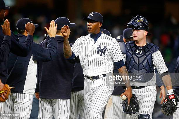 Aroldis Chapman and Brian McCann of the New York Yankees celebrate with their teammates after defeating the Kansas City Royals at Yankee Stadium on...