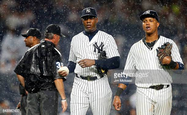 Aroldis Chapman and Starlin Castro of the New York Yankees walk off the field during a ninth inning rain delay against the Texas Rangers at Yankee...