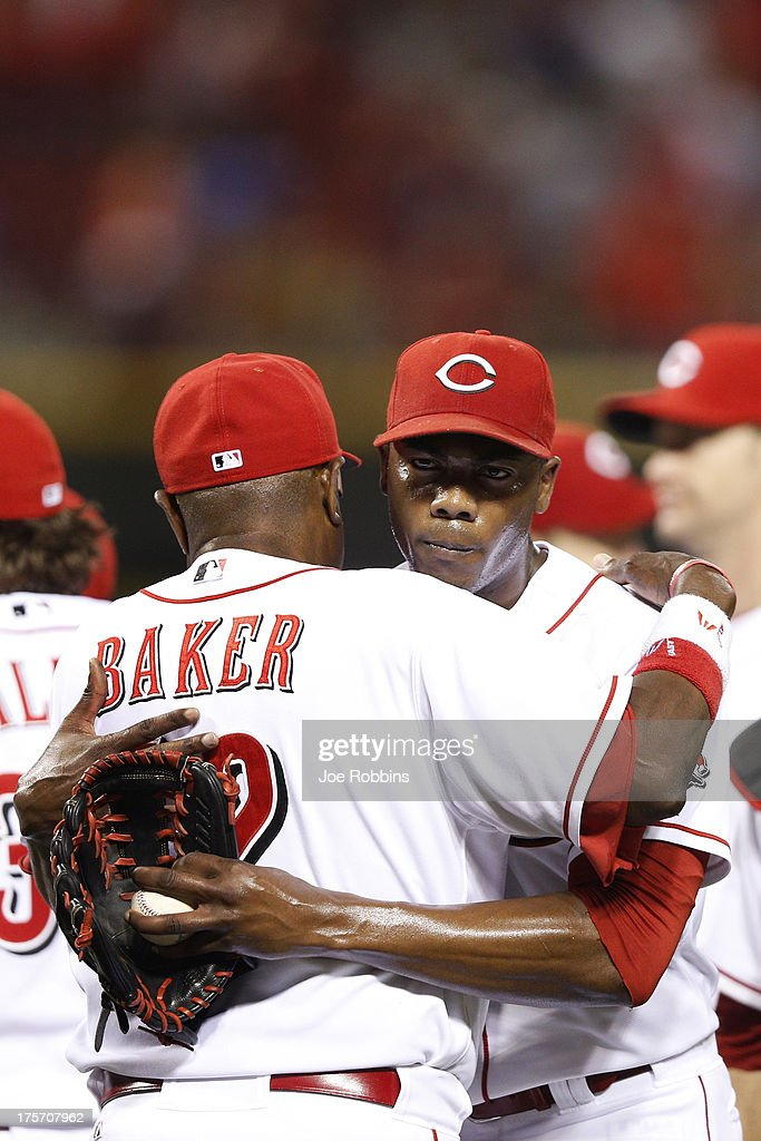 Aroldis Chapman #54 of the Cincinnati Reds gets a hug from manager Dusty Baker after the game against the Oakland Athletics at Great American Ball Park on August 6, 2013 in Cincinnati, Ohio. The Reds won 3-1.