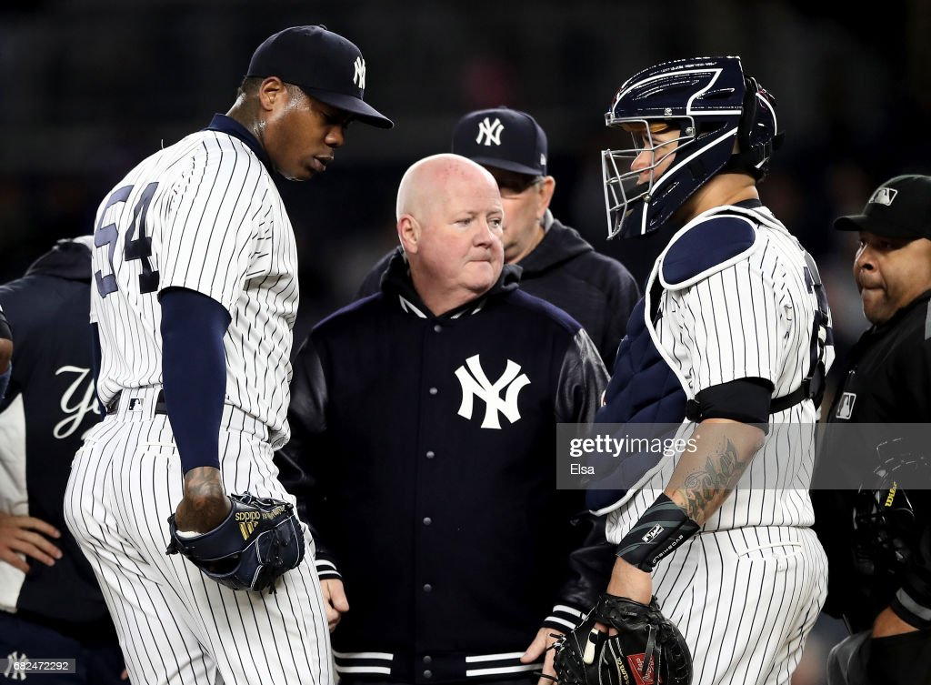 Aroldis Chapman #54 of the New York Yankees is checked out by New York Yankees staff in the ninth inning as teammate Gary Sanchez #24 looks on on May 12, 2017 at Yankee Stadium in the Bronx borough of New York City.