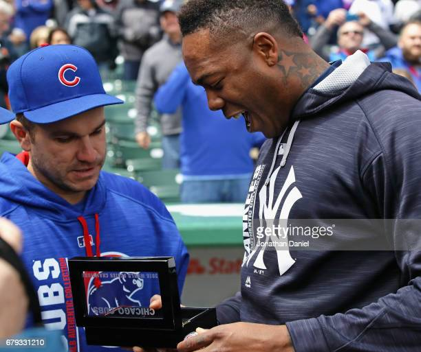 Aroldis Chapman of the New York Yankees looks over his World Series ring with Miguel Montero of the Chicago Cubs before a game at Wrigley Field on...