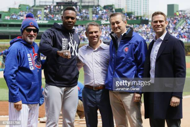 Aroldis Chapman of the New York Yankees shows off his World Series ring with Manager Joe Maddon general manager Jed Hoyer owner Tom Ricketts and...