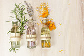 Essential oils for aromatherapy and massage.  Row of essential oils in glass bottles, rosemary, lavender and calendula, on the wooden board.