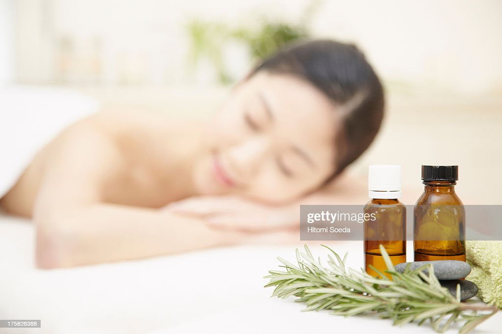 Aromatherapy oils with woman in background : Stock Photo