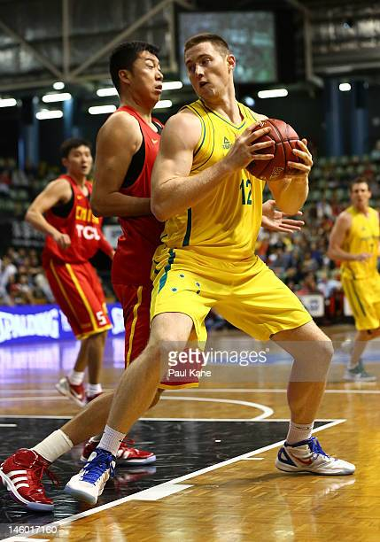 Aron Baynes of the Boomers looks step around Zhizhi Wang of China during game one of the international friendly series between the Australian Boomers...