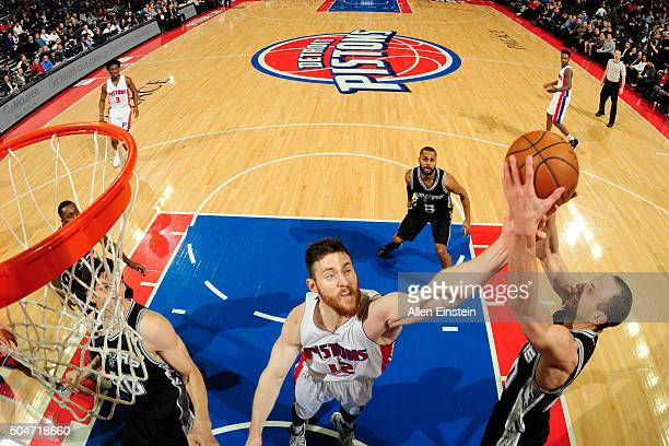 Aron Baynes of the Detroit Pistons and Manu Ginobili of the San Antonio Spurs go after a rebound on January 12 2016 at The Palace of Auburn Hills in...