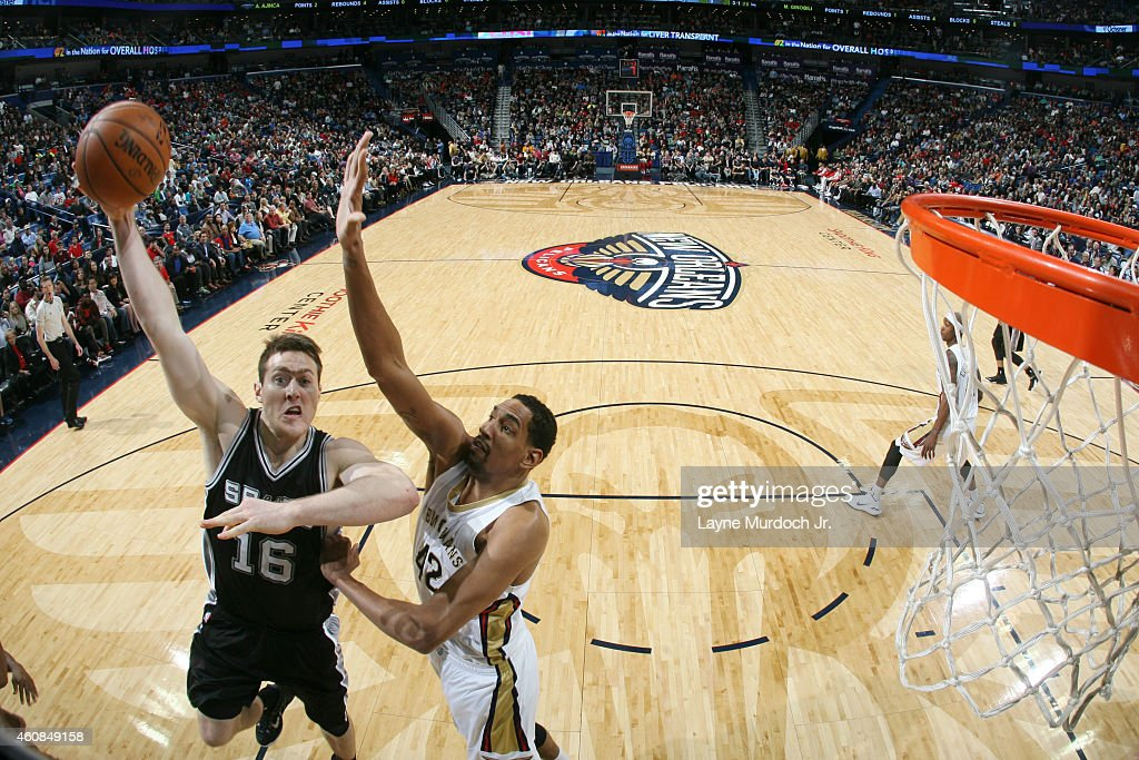 Aron Baynes #16 of the San Antonio Spurs shoots against Alexis Ajinca #42 of the New Orleans Pelicans on December 26, 2014 at Smoothie King Center in New Orleans, Louisiana.