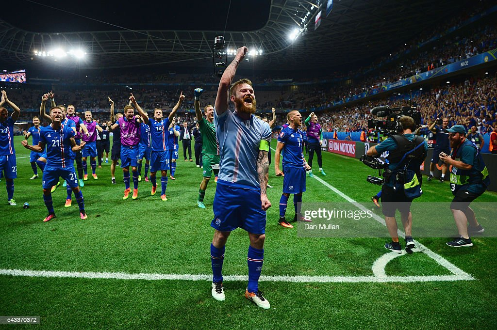 Aron Gunnarsson (C) and Iceland players celebrate their team's 2-1 win with supporters after the UEFA EURO 2016 round of 16 match between England and Iceland at Allianz Riviera Stadium on June 27, 2016 in Nice, France.
