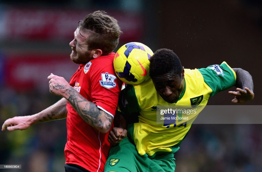 Aron Gunnarsson of Cardiff City goes up for a header with Alex Tettley of Norwich City during the Barclays Premier League match between Norwich City...