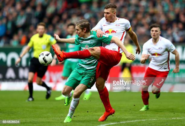 Aron Johannsson of Bremen is challenged by Willi Orban of Leipzig during the Bundesliga match between Werder Bremen and RB Leipzig at Weserstadion on...
