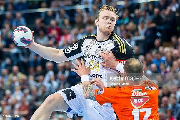 Aron Palmarsson of Kiel challenges Szabolcs Zubai of Szeged during the VELUX EHF Champions League Quarter Final between THW Kiel and Pick Szeged at...