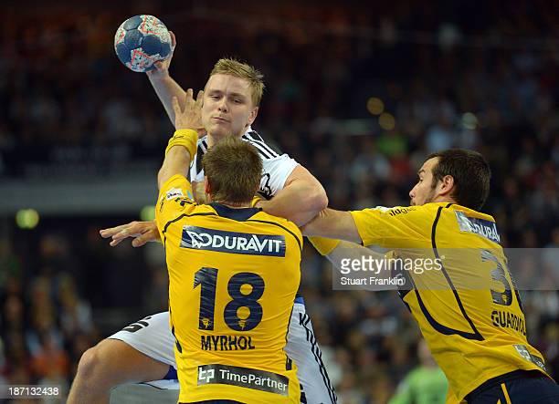 Aron Palmarsson of Kiel is challenged by Bjarte Myrhol and Gedeón Guardiola of Rehein Neckar during the Bundesliga handball match between THW Kiel...