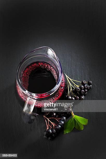 Aronia juice in carafe, chokeberries on slate