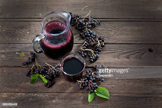 Aronia juice in carafe, glass and chokeberries on wood