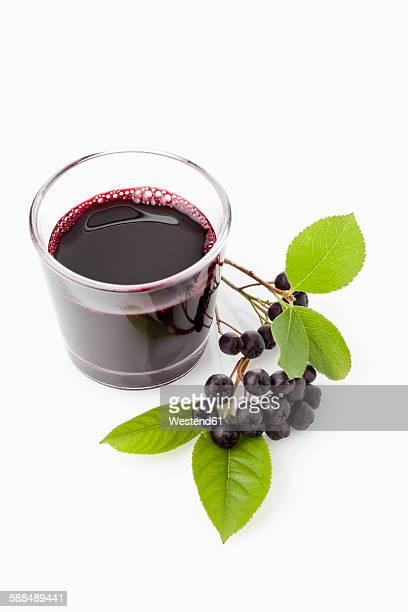 Aronia juice in glass, chokeberries