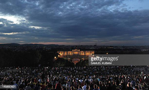 Around 100000 people watch the Vienna Philharmonic Orchestra perform during an open air 'Summer Night' concert backdropped by Schoenbrunn Palace in...