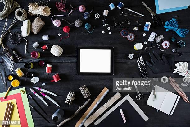 Arrangement of craft materials, tools and digital tablet on black wood