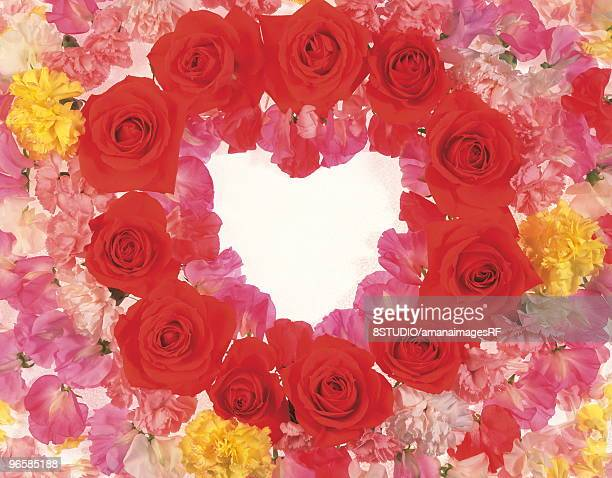Arrangement of many flowers and petals to make a heart shape