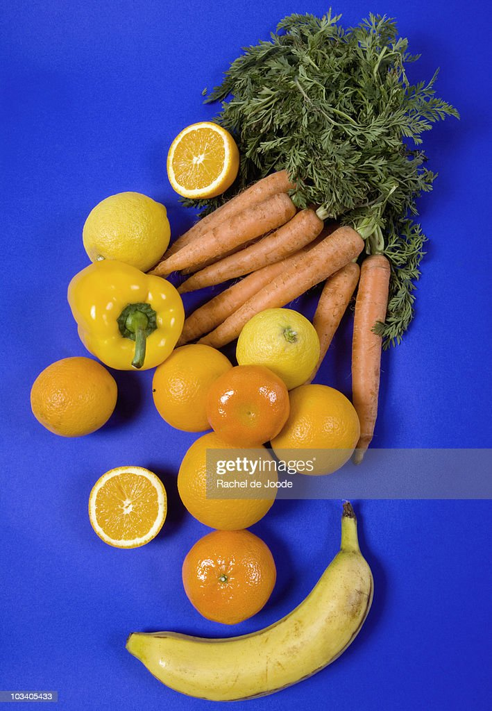 Arrangement of orange and yellow fruits and vegetables on a blue background : Stock Photo