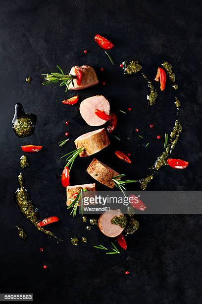 Arrangement of veal slices, basil pesto, slices of red bell pepper and red peppercorns on black background