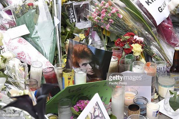 Array of votive candles and pictures left in front of Bowie home in SoHo Hundreds of New Yorkers filed quietly in front of singer David Bowie's SoHo...