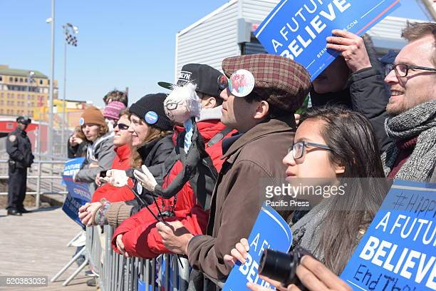 Arrayed with buttons stickers signs Sanders supporters listen to candidate's speech Democratic presidential candidate Bernie Sanders addressed...