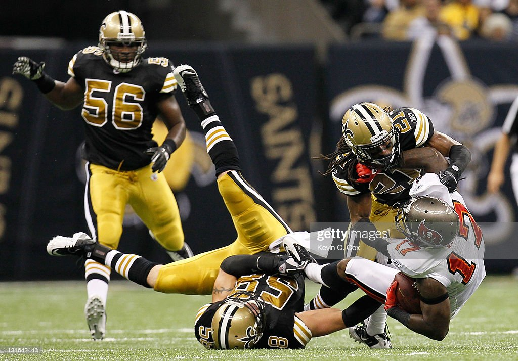 Arrelious Benn #17 of the Tampa Bay Buccaneers is tackled by Scott Shanle #58 and Patrick Robinson #21 of the New Orleans Saints at Mercedes-Benz Superdome on November 6, 2011 in New Orleans, Louisiana.