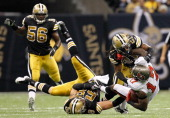 Arrelious Benn of the Tampa Bay Buccaneers is tackled by Scott Shanle and Patrick Robinson of the New Orleans Saints at MercedesBenz Superdome on...
