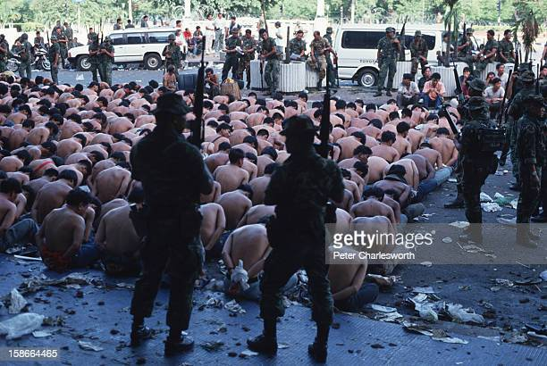 Arrest of prodemocracy demonstrators Shirtless young men with their hands tied behind their backs sit outside the Royal Hotel guarded by Thai Army...