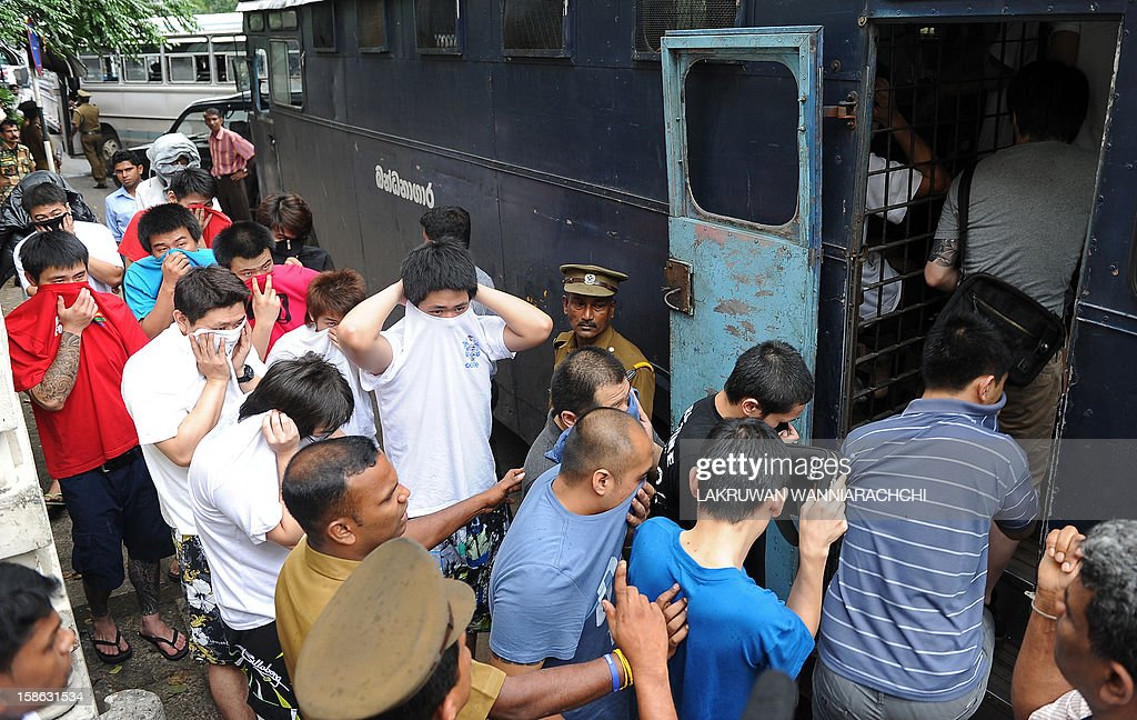 Arrested Chinese nationals are escorted by Sri Lankan police as they are taken to a remand prison after being produced before the magistrate court in Colombo on December 22, 2012. Police in Sri Lanka on Saturday said had arrested 100 Chinese nationals for currency fraud in a string of raids in and around the capital Colombo in what they described as a case of cyber-crime.