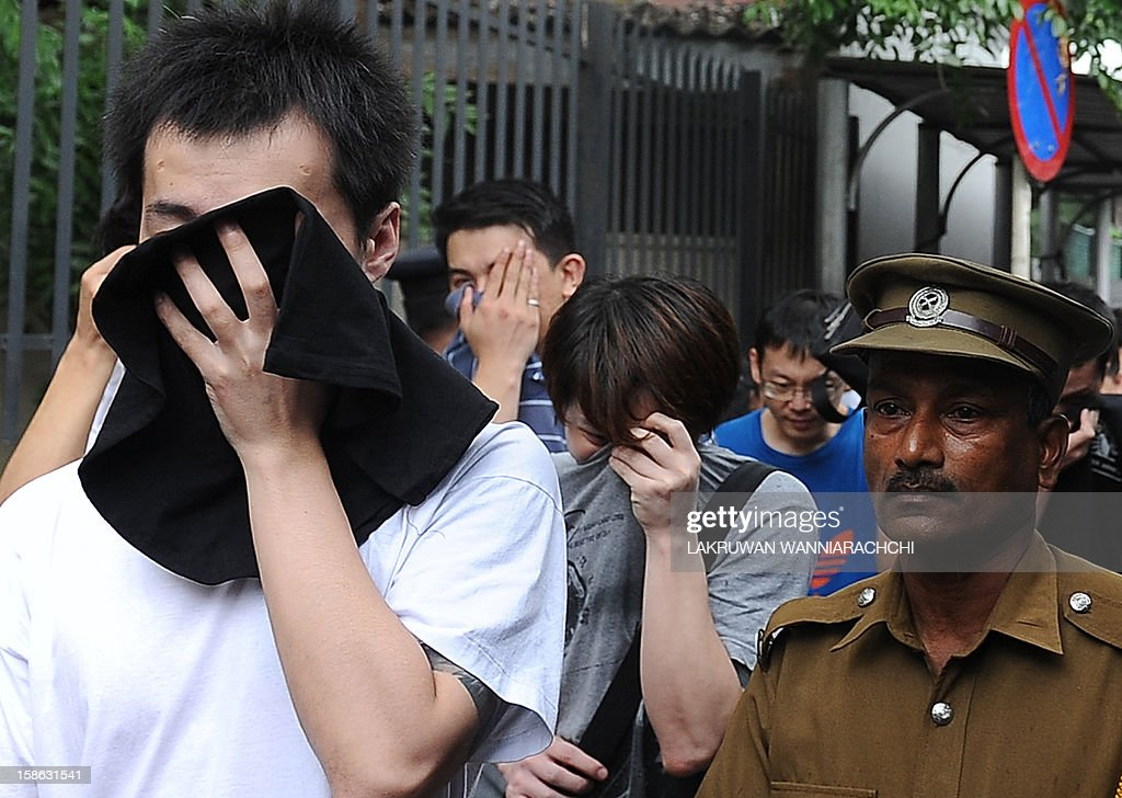 Arrested Chinese nationals are escorted by Sri Lankan police as they are taken to a remand prison after being produced before the magistrate court in Colombo on December 22, 2012. Police in Sri Lanka on Saturday said had arrested 100 Chinese nationals for currency fraud in a string of raids in and around the capital Colombo in what they described as a case of cyber-crime. AFP PHOTO/ LAKRUWAN WANNIARACHCHI