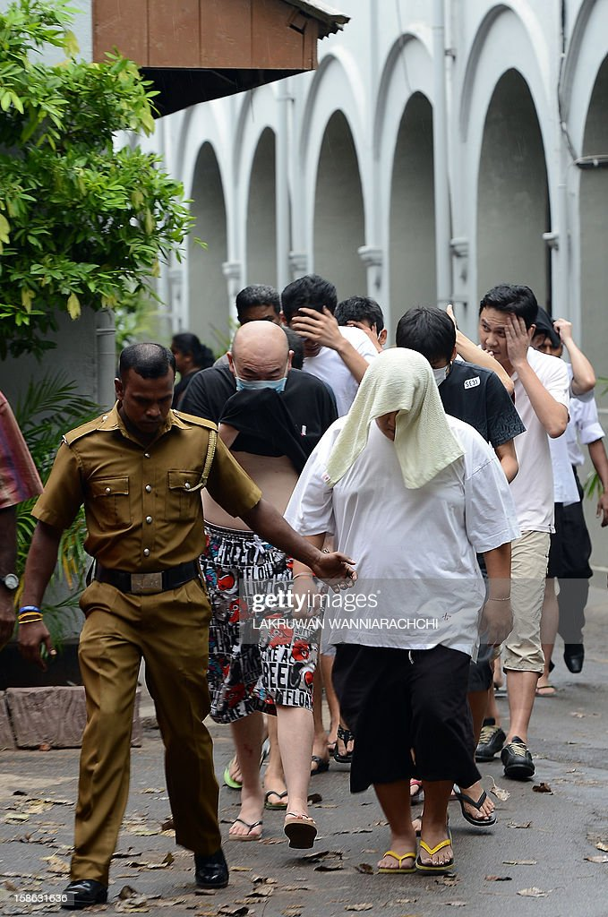 Arrested Chinese nationals are pictures outside the Sri Lankan magistrate court in Colombo on December 22, 2012. Police in Sri Lanka on Saturday said had arrested 100 Chinese nationals for currency fraud in a string of raids in and around the capital Colombo in what they described as a case of cyber-crime.