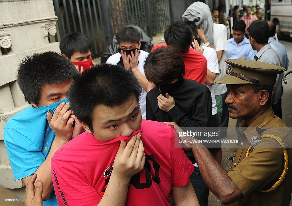 Arrested Chinese nationals are taken to a remand prison after being produced before the magistrate court in Colombo on December 22, 2012. Police in Sri Lanka on Saturday said had arrested 100 Chinese nationals for currency fraud in a string of raids in and around the capital Colombo in what they described as a case of cyber-crime.